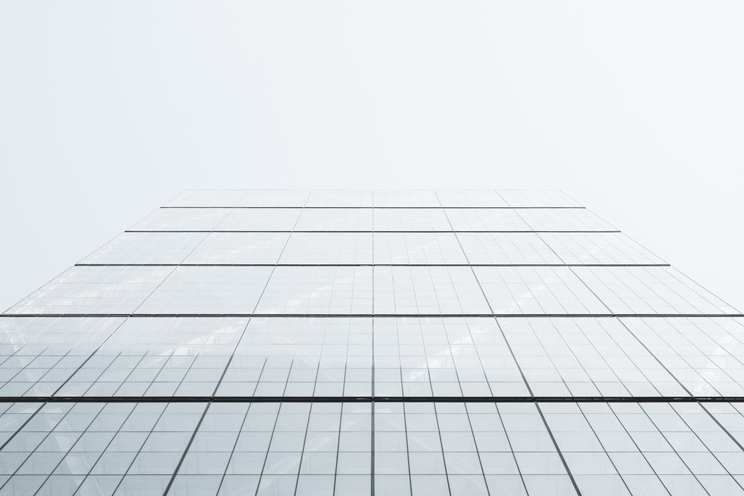 image of the side of glass building that fades into the sky