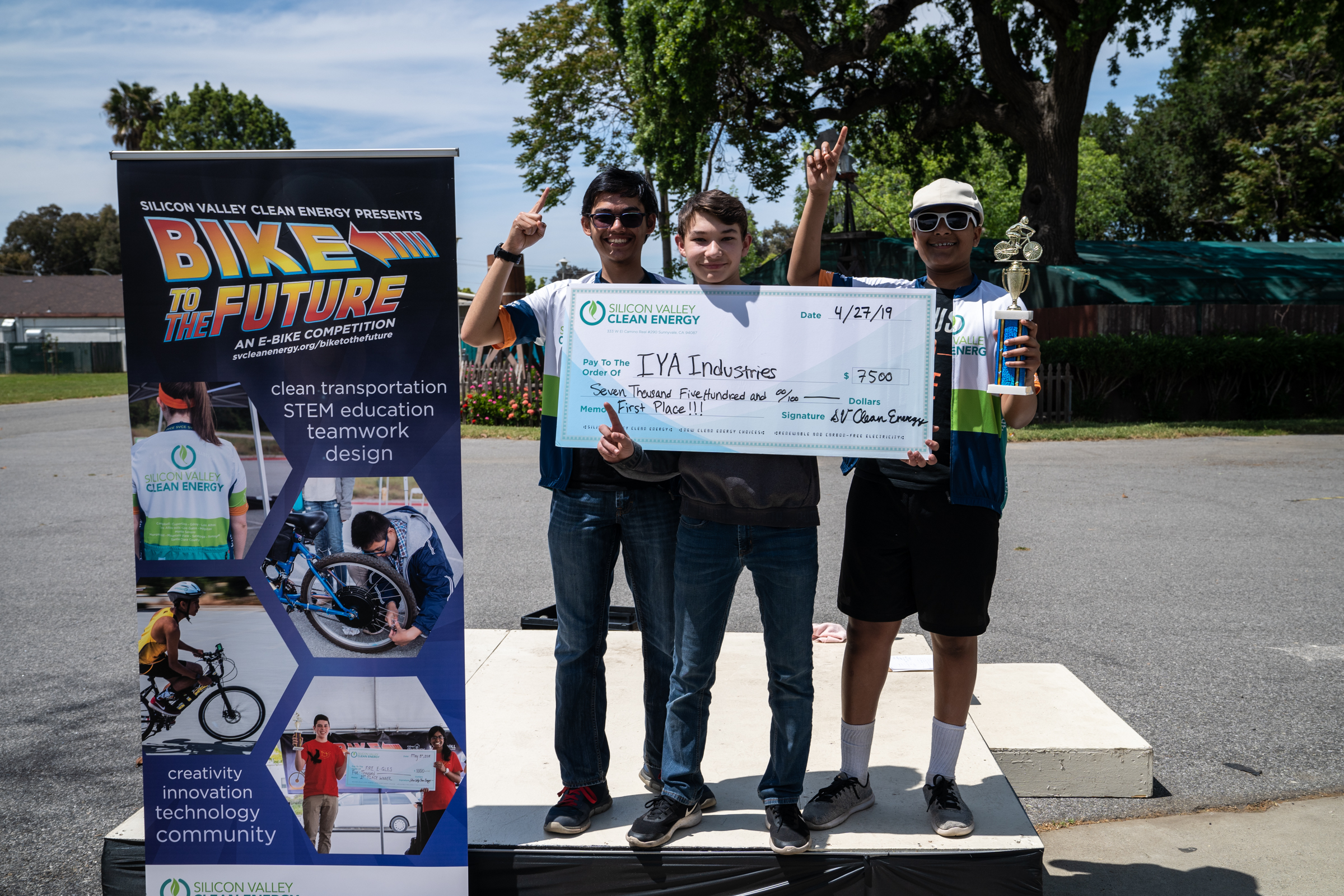 Winning Team of three high school boys holding trophy and giant check