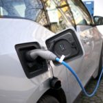 close-up of electric vehicle charger plugged into a white electric vehicle
