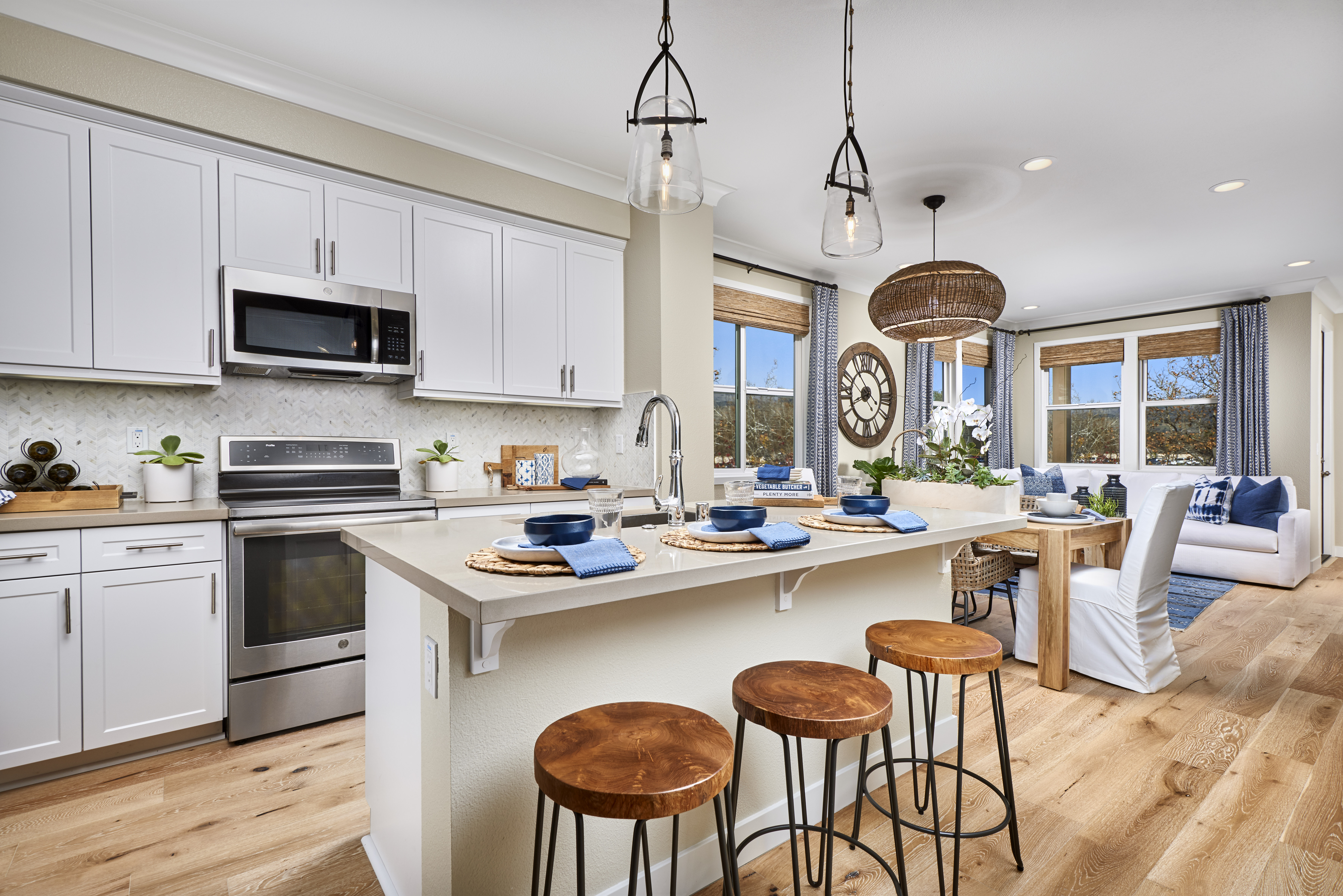 Interior shot of modern kitchen with light wood floors, unique light fixtures, white furniture with blue accents