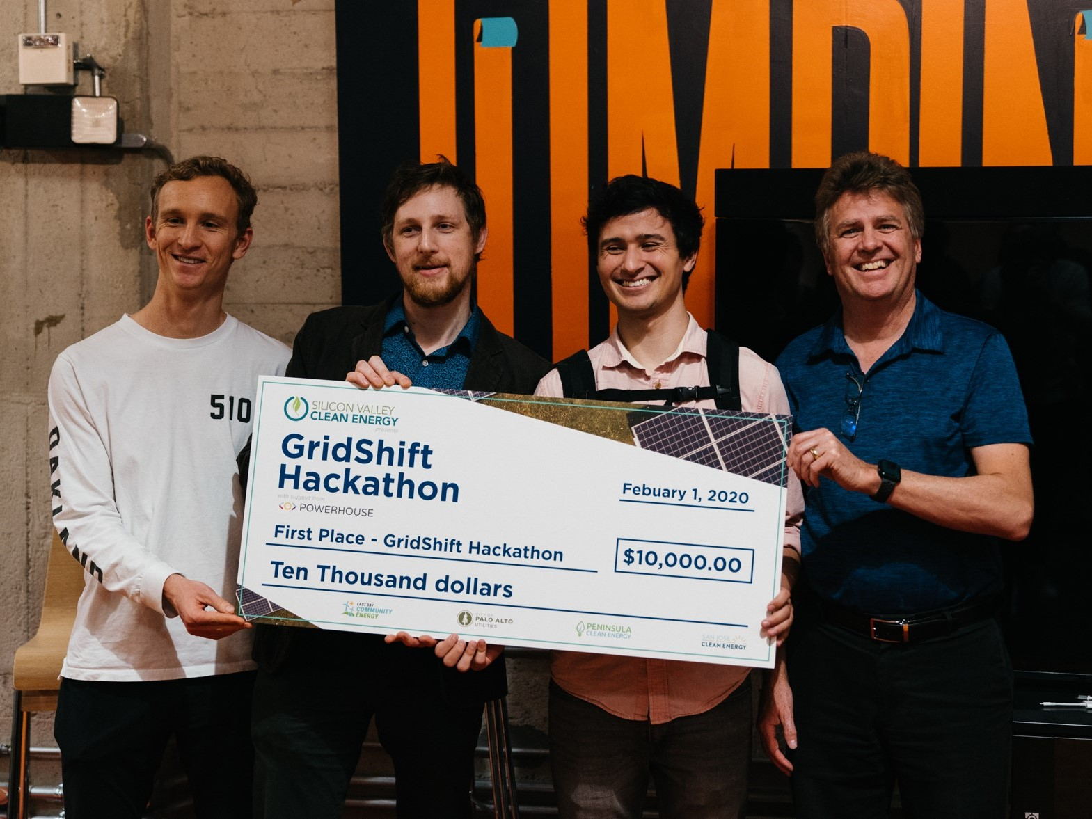 Four men holding a large $10,000 check - excited